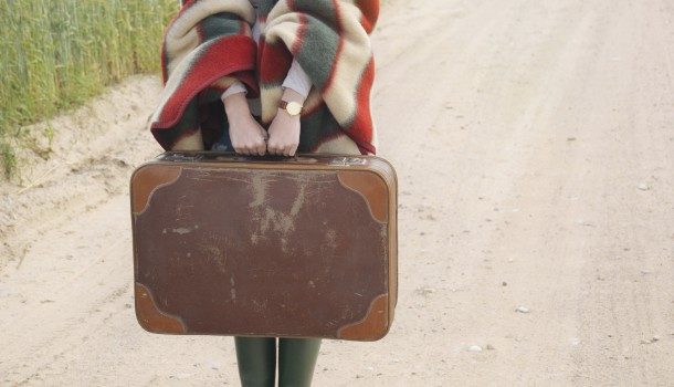 women's hands hold old suitcase at autumn outdoor on the country