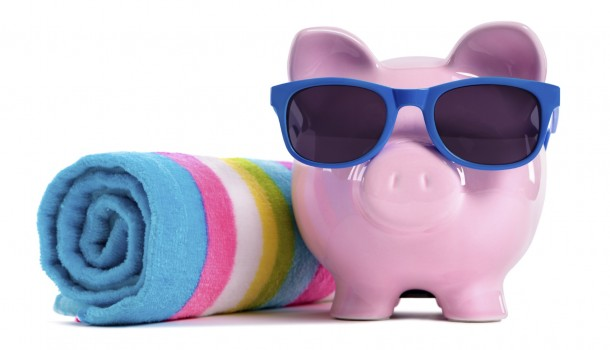 Pink piggy bank with blue sunglasses and candy stripe beach towel.