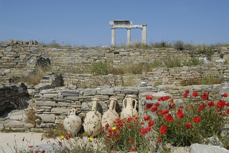 Delos island, Greece, is an important archeological site with numerous old ruins. In this photo ancient stone walls, earthenware urns and architectural columns are visible with red poppies flowering in the foreground. Photo taken in springtime against clear blue sky. Horizontal color image with copy space.