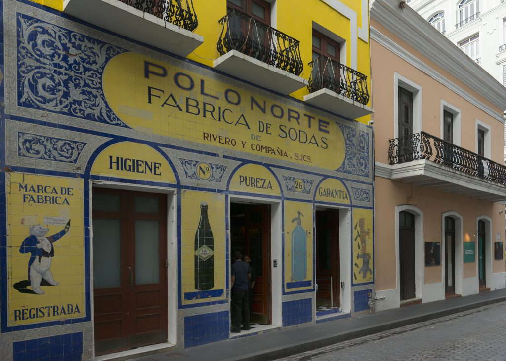San Juan, Puerto Rico - March 13, 2015: The historic colorfully tiled facade of an old soda maker business in Old San Juan. Figurative and non figurative images. Yellow and blues are dominant.
