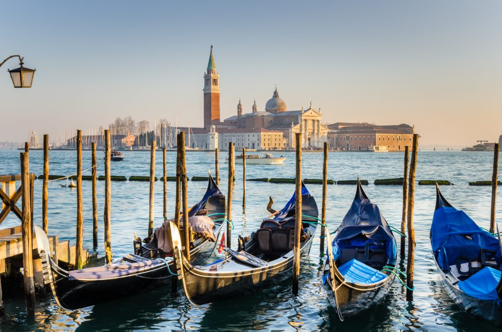 Photo of Venice at Sunset. Some traditional gondolas, tied up to the quay in Saint Mark's square, are in foreground while Saint George Island, one of the island of Venice, is visible in background.