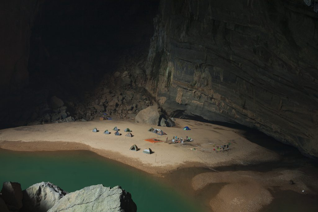 Campsite close to the green blue water in the Hang En cave, Phong Nha-Kẻ Bàng National Park