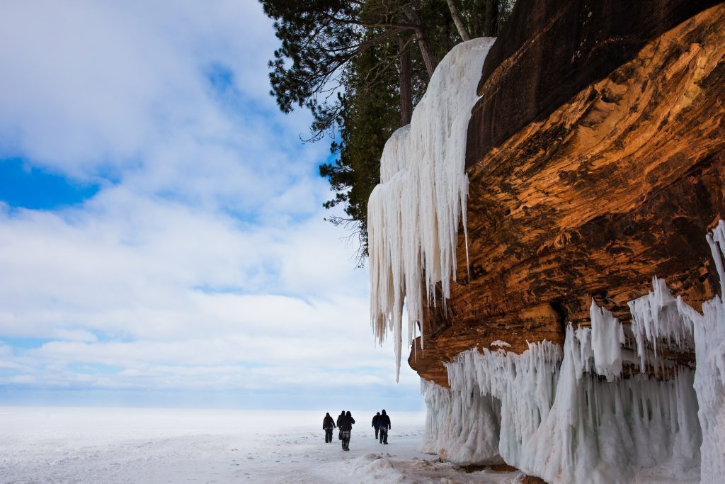 Frozen Lake Superior shoreline in winter showing an orange stone cliff, large icicles, the frozen lake, and people for scale. There is copy space on the left side of the frame. Photograph is from the Apostle Islands National Lakeshore on Lake Superior in Northern Wisconsin, a popular winter travel destination.